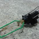 Kocher Optimus Vega: zusaamengeklappter Kartuschenfuß und Flammenregulierer (grüner Drahtbügel)