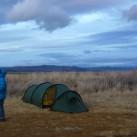 Angemessen warm verpackte Camperin nebst Hammer-Zelt und imposanter Wolkenkulisse