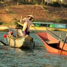 Einheimische ernten Seegras mit riesigen Essstäbchen, während die Kinder das Wasser aus dem Boot schöpfen.