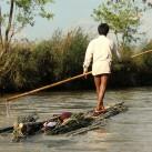 Bambus wird in einem Kanal zum nächsten Dorf transportiert, während eine Frau ihre Kleidung wäscht (Myanmar).