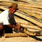 Ein Bauer sägt das Bambusgerüst für die Rekonstruktion des Tempels zurecht. Von den Füßen aufwärts wechselt das Farbspektrum der Haut in einen intensiven Rotton. Anscheinend verbrennen sich auch Einheimische (Mandalay, Myanmar).