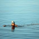 Ein Fischer watet Schultertief durch das Wasser, um den besten Spot zum Angeln zu erreichen (Mandalay, Myanmar).