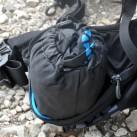 Die Regenhülle steckt in einem kleinen Packsack, beides hat Platz in der elastischen Hüfttasche