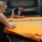 Überstehender Stoff wird nach dem Laminieren von Hand weggeschnitten
