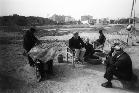 Uiguren beim Rasieren vor der abgerissenen Altstadt